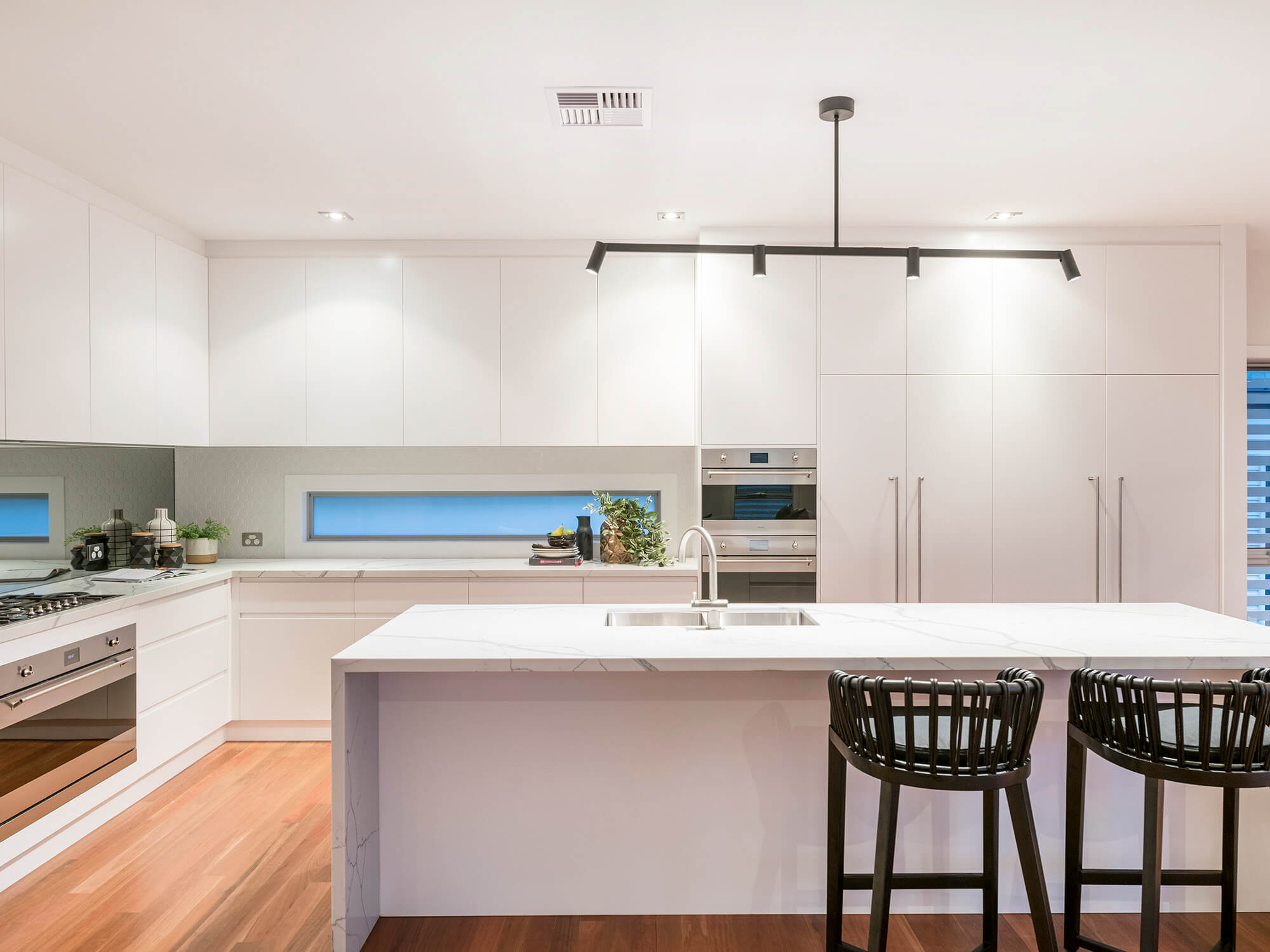 Modern white kitchen with marble benchtops after renovations